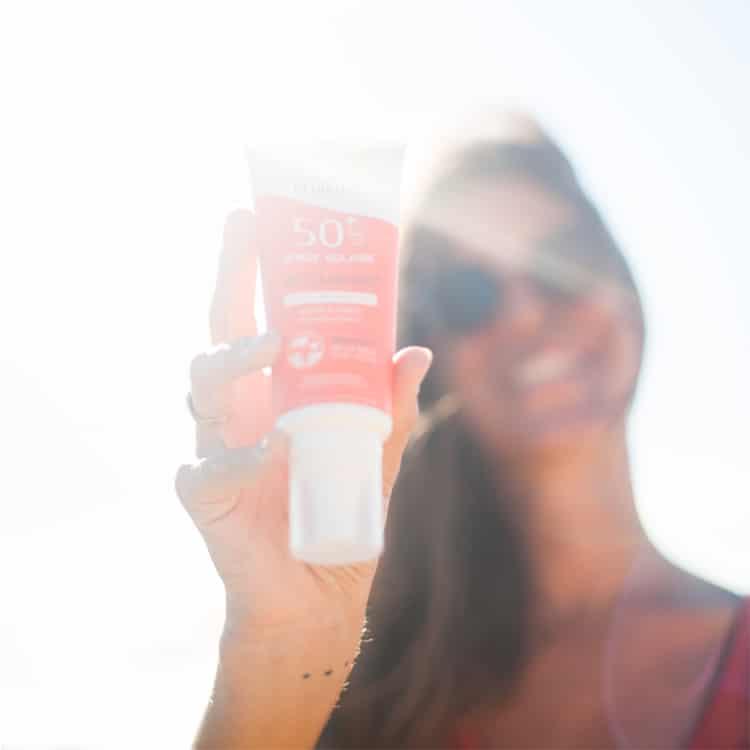 femme qui tient du spray solaire bio