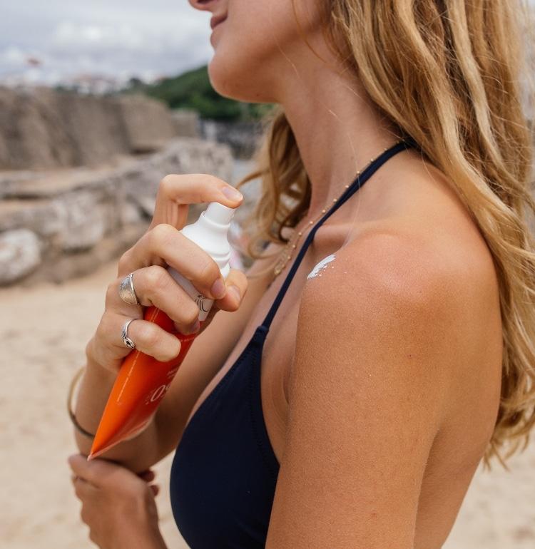 une femme s'applique de la crème solaire Bio