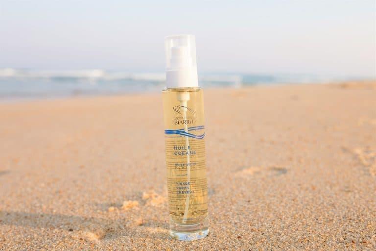 huile océane posée dans du sable avec l'océan en arrière plan