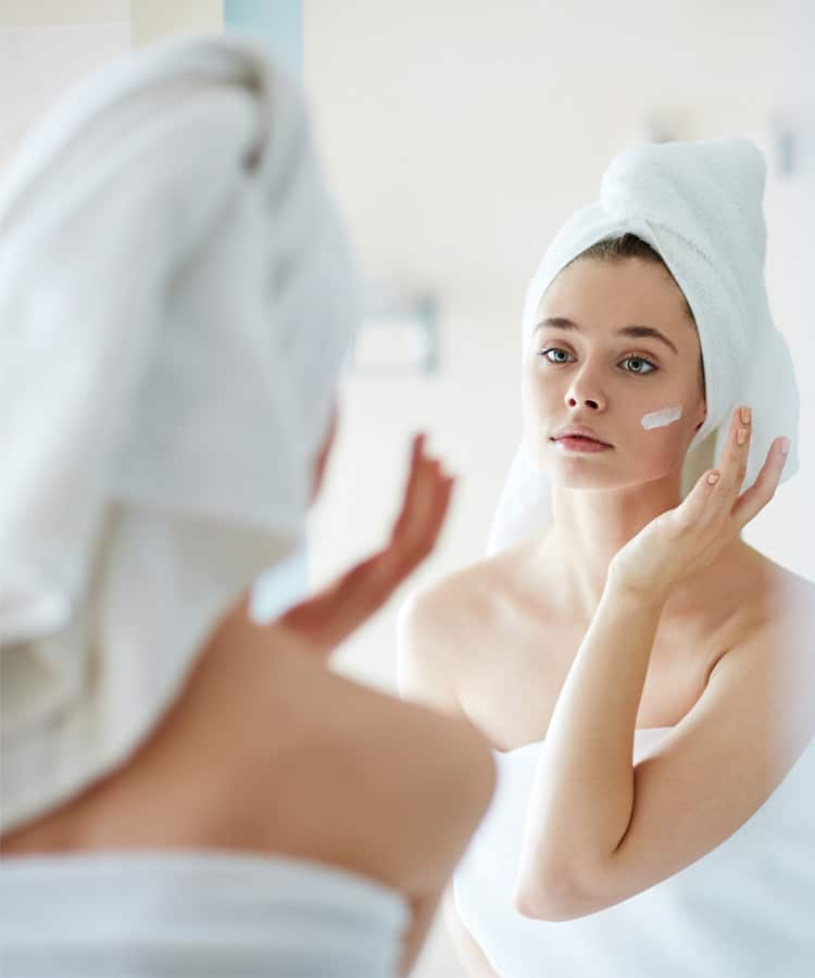 femme qui s'applique de la crème sur le visage