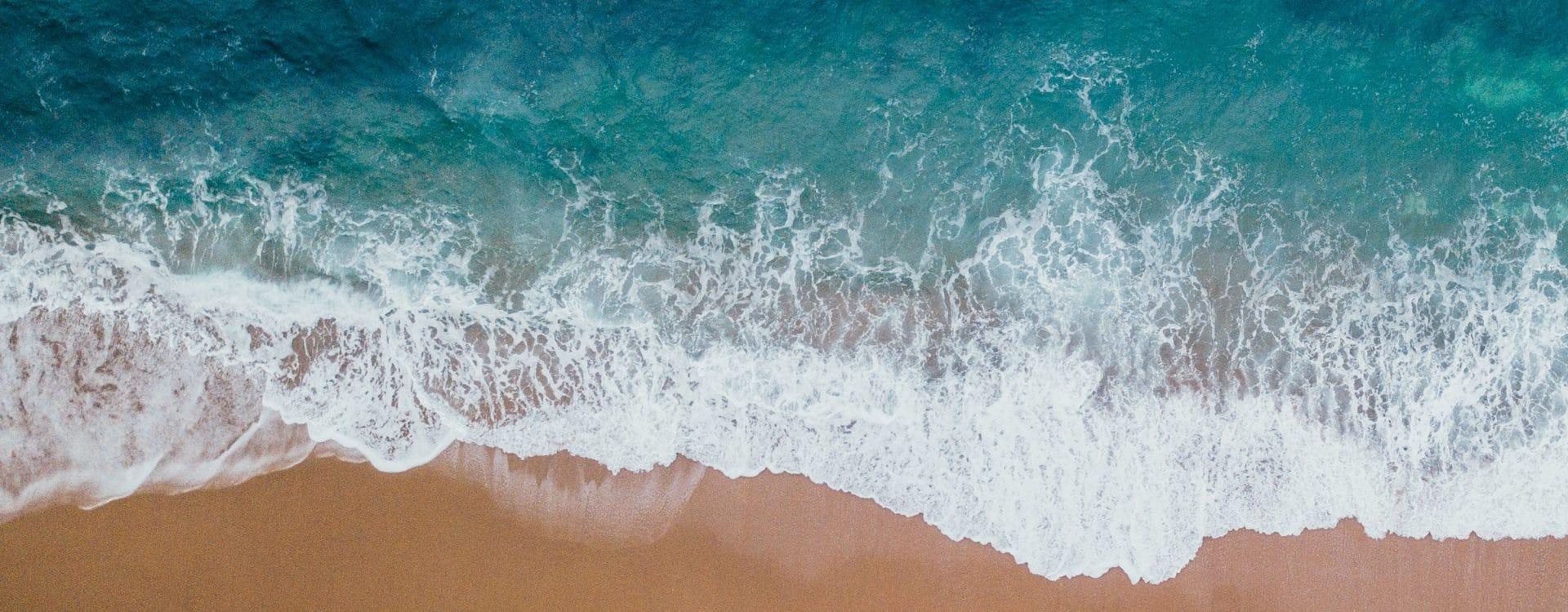 vague qui casse sur le sable vue en drone