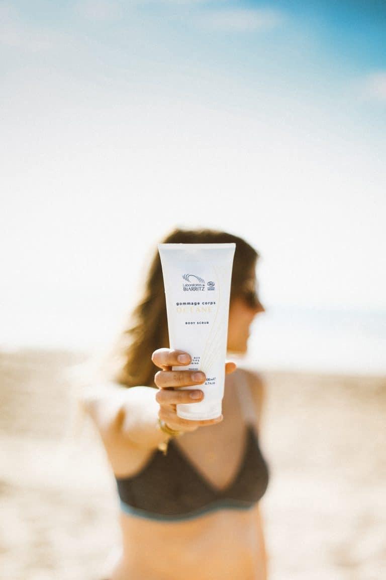 Femme qui tient le gommage bio pour le corps de la gamme océane