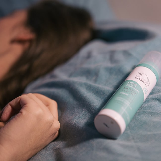 femme qui dort près d'une crème de nuit